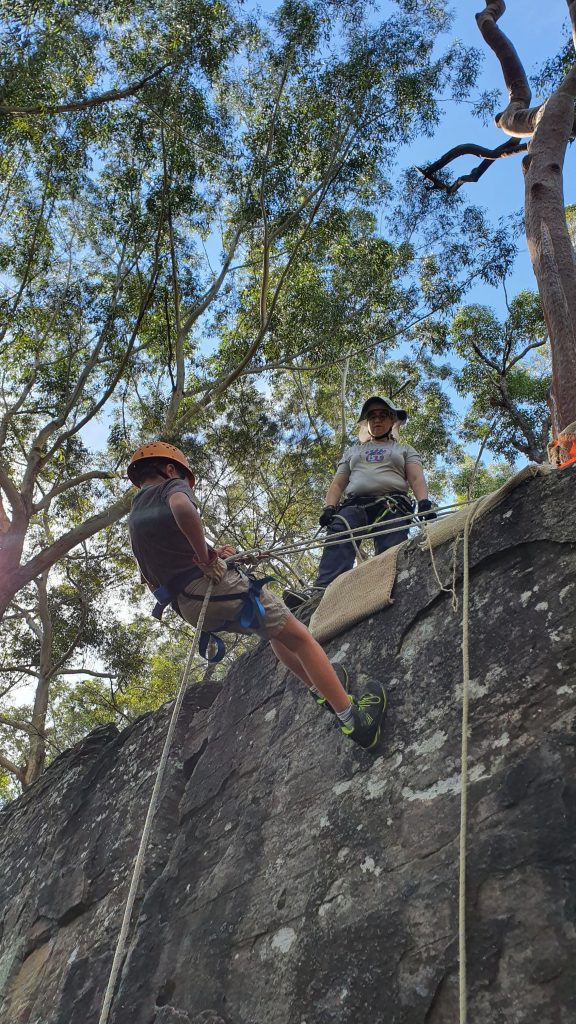 A Scout abseils on a top belay at Lindfield Rocks