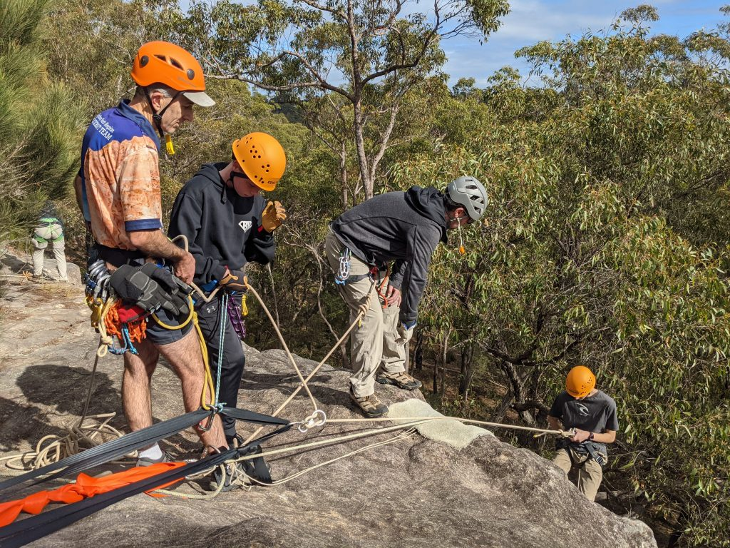 A Venturer Operates a top belay supervised by an Abseil Guide, whilst another Venturer is Abseiling at a Basic Rockcraft Abseil Course.
